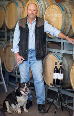 Winemaker, Paul Smith, with Spot the dog and barrels and bottles of their fine vintage wines