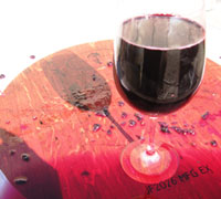 glass of wine sitting on a barrel
